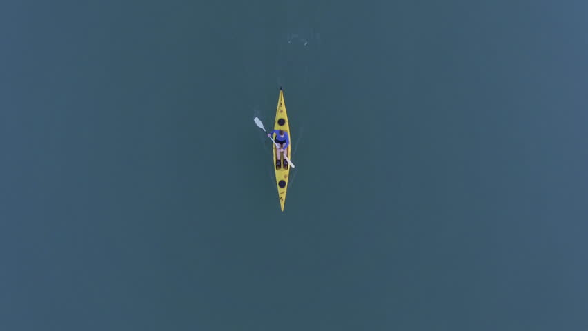 Top down aerial shot of solo kayaker in yellow kayak paddling forwards, camera moves out to reveal landscape