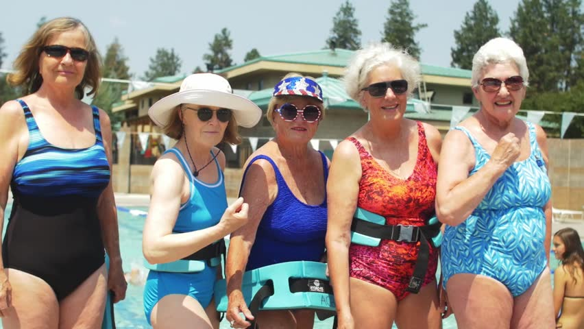 Five adorable old ladies wearing festive bathing suits and sunglasses stand by the pool, and flex their muscles at the camera   Shutterstock HD Video #1015666162