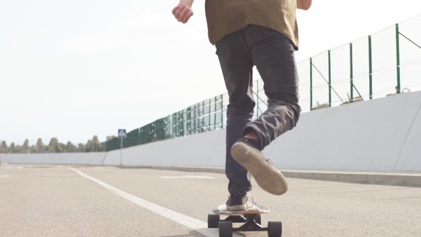 Sports Man skateboarding in Park in summer morning. man rides longboard #1015674832