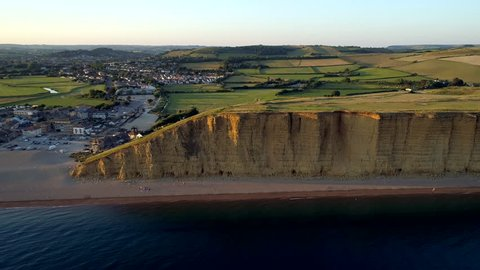 Drone tracks sideways along the cliff and beach in West Bay in the Dorset countryside. Shot during sunset