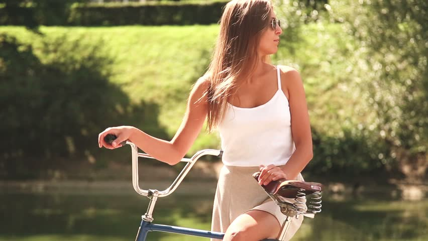 A tanned young woman in sunglasses in  white T-shirt and in a gray skirt ride a vintage bicycle in park. A girl with a scar.