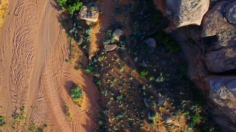 4K aerial overhead view of a pickup truck driving down a remote desert ranch road. The sun is low and casts long shadows from the unique landscape.