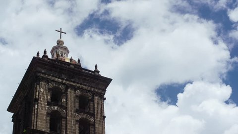Time lapse of clouds streaming by the tower of an ancient Mexican Cathedral