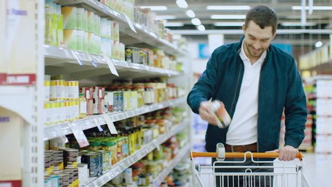 At the Supermarket: Handsome Man Browses Through Shelf with Canned Goods, Chooses Tin Can and Places it into His Shopping Cart. Shot on RED EPIC-W 8K Helium Cinema Camera.