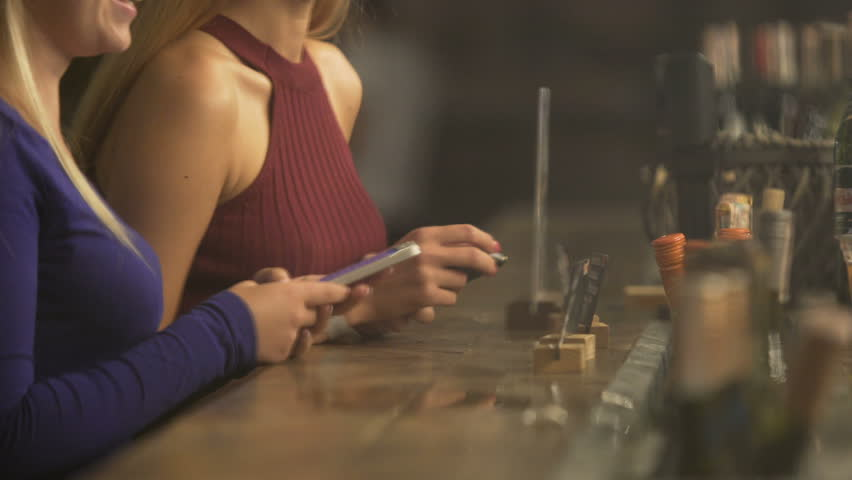 Attractive females ordering drinks at bar counter, flirting with bartender