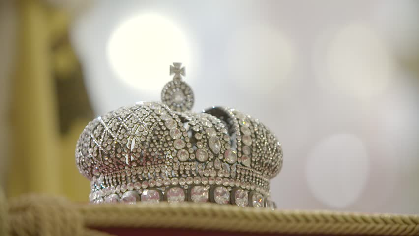 Gold and jewell-studded King's crown on a ceremonial pillow