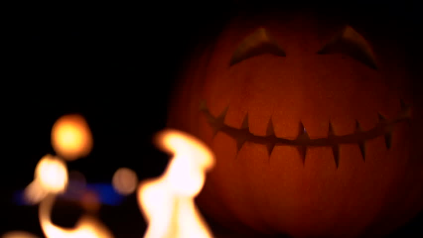 Fearful symbol of Halloween - Jack-o-lantern. Scary smiling head of pumpkin in inferno fire flames. Half of orange gourd on the right side. Glowing face, trick or treat. Slow motion.