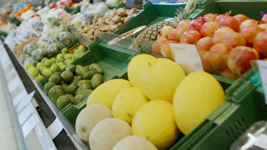 At the Supermarket: Gliding Shot of the Fresh Produce Section of the Store. Exotic Fruits and Organic Vegetables on Sale in the Farmer's Market. Shot on RED EPIC-W 8K Helium Cinema Camera. | Shutterstock HD Video #1015805062