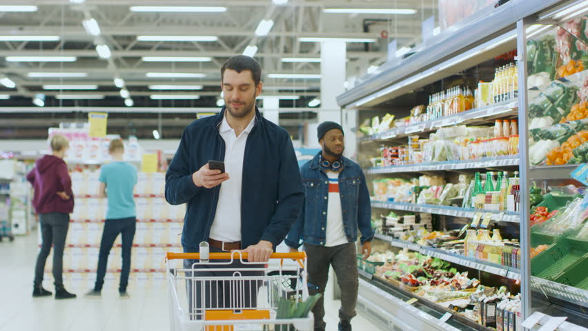 At the Supermarket: Handsome Man with Smartphone, Pushes Shopping Cart, Walks Through Fresh Produce Section of the Store, Chooses Some Products. Shot on RED EPIC-W 8K Helium Cinema Camera. | Shutterstock HD Video #1015805122