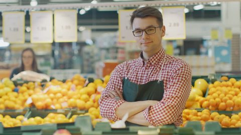 At the Supermarket: Portrait Of the Handsome Stock Clerk Wearing Apron, Arranging Organic Fruits and Vegetables, He Smiles and Crosses Arms. Friendly, Efficient Worker. Shot on RED EPIC-W 8K Camera.