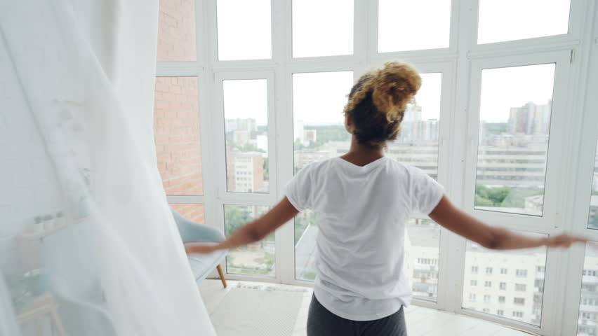 Back view of African American woman walking to panoramic window, parting curtains and looking outside enjoying view of big modern city. Accommodation and people concept.
