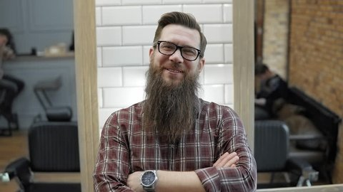 Barber and his happy customer in barbershop. Grooming the beard. Hairdressers in the workplace. Beard hairstyling and haircutting in a barber shop.