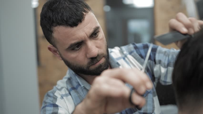 Close-up of barber cuts the hair by scissors at barbershop. Hairdresser's hands at working process. Barber making haircut of attractive bearded man in barbershop. Hairdresser at work. Beauty saloon. | Shutterstock HD Video #1015820512