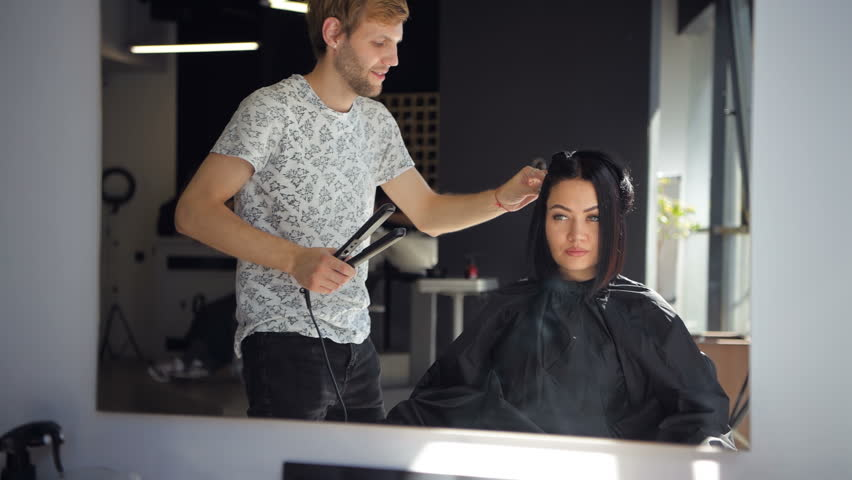 Close up. Female hairdresser straighten brown hair to woman using hair iron in beauty salon. Female stylist makes hairstyle for young beautiful woman in hairdressing salon.