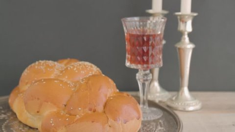 Shabbat or Sabbath kiddush ceremony composition with a traditional sweet fresh loaf of challah bread, glass of red kosher wine and candles on a vintage wood background. Tilt camera action