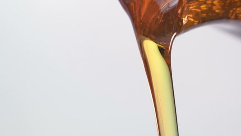 Motor oil pouring on white background.