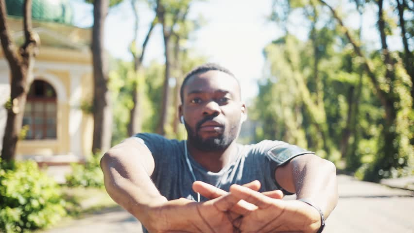 Portrait african american man doing exercise listen music in headphones look at camera walk at park close up training active athlete body fit health sport workout runner summer app muscular jogging | Shutterstock HD Video #1015886902