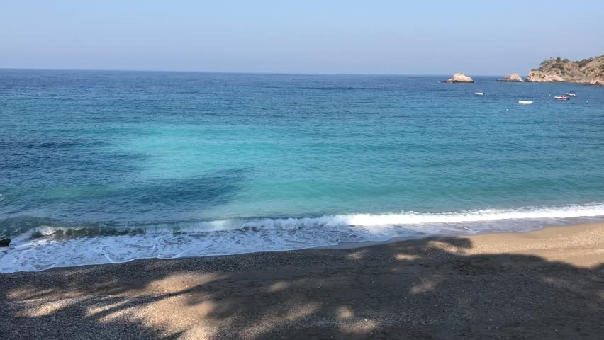 Sea waves at beach in a cove. small boats floating in sea. Isolated shore.