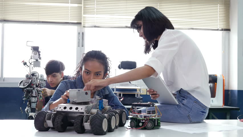 Team engineer talking how to develop robot at laboratory. Creative designer team working together with robotics prototype project in workshop. People with technology or innovation concept. 4K Resoluti
