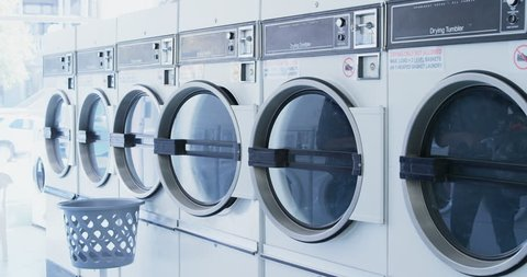 Woman putting clothes into washing machine at laundromat 4k