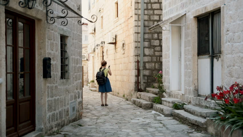 Young happy woman traveling at Montenegro and looking Perast landmarks, hipster girl with map at the city center make a photo. Vacation and travel concept. #1015959172