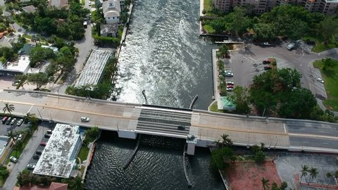 Drone flying over a bridge in Boca Raton, Florida flanked by luxury homes.