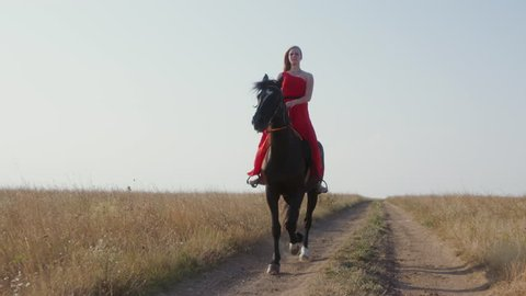 Young girl in long red dress riding black horse across field in summer