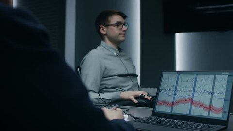 Young Handsome Suspect During Interrogation Undergoes Lie Detector / Polygraph Test, Connected to the Machine He Answers Questions. Computer Shows Measures of Physiological Responds. Shot on 4K UHD.