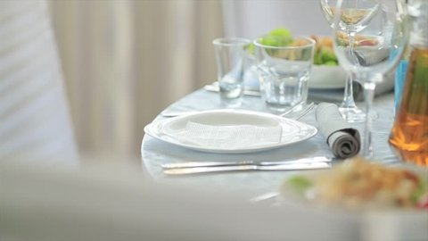waiter brings dish with salad in restaurant puts plate on covered with white tablecloth, cutlery and dishes are on table in cafe Caesar salad is served on table.