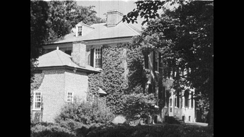 1930s: UNITED STATES: Ivy grows up side of house. Old rural houses in America. Rural farmhouse. Georgian building and garden.