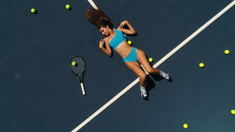 the girl in sports lingerie on the tennis court top view.