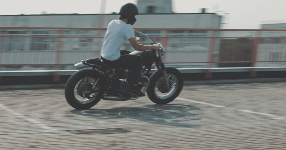 Motorcyclist drives on a motorcycle on the road in the city. Biker rides a vintage custom motorbike from 1970s . Urban lifestyle scene. 4K video shooting by handheld gimbal | Shutterstock HD Video #1016028772