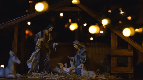 Jesus Christ Nativity scene with atmospheric lights and candles. Jesus Christ birth in a stable with Mary and Joseph figures. Christmas scene. 4k