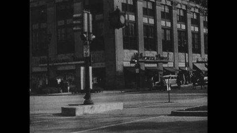 1940s: Pedestrians cross busy city street. Men, women and children window-shop on city street. Man refuels car at service station. People walk past movie theater.