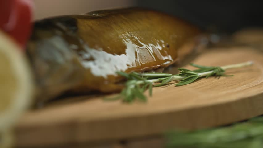 The chef smears smoked fish with oil before serving via silicone culinary brush. Restaurant or cafe kitchen. Wooden table, fish cooked in smokehouse, cutting board, leek, lemon, thyme. Macro shot | Shutterstock HD Video #1016047672