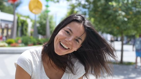 Beautiful young brunette woman acting happily, cheerfully smiling and jumping, laughing to camera while running cross the sunny city park. Positive emotions