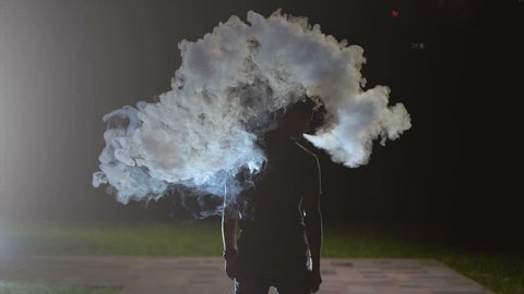 The man smoking an electronic cigarette. evening night time, slow motion