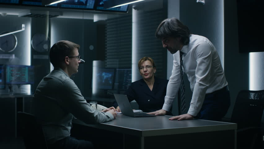 Male and Female Special Service Agents Interrogate Young Suspect in Cyber Crimes, Officer Looses Temper and Threatens Accused while Questioning. Dark Interrogation Room. Shot on RED EPIC-W 8K Camera.