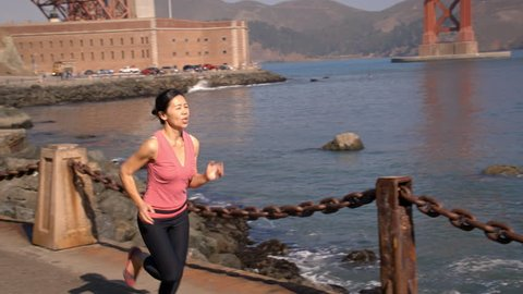 Asian woman jogs in San Francisco. The Golden Gate Bridge can be seen in the background.