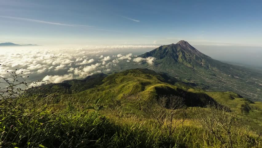 Timelapse of morning clouds rolling over  Merapi volcano nearby Yogyakarta, Java, Indonesia. The shot is taken from the neighbour volcano of Merbabu and its ridge is visible in foreground of the shot.
