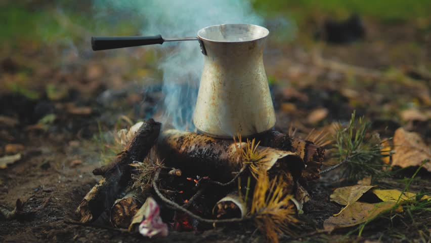 Making coffee in cezve on fire. fire in a beautiful autumn forest. Camp Fire.
