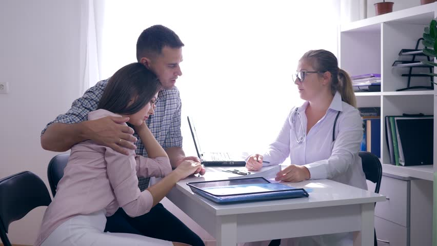 Women health, gynecologist doctor talking of infertility to a young upset couple in a white medical office in a hospital | Shutterstock HD Video #1016145712