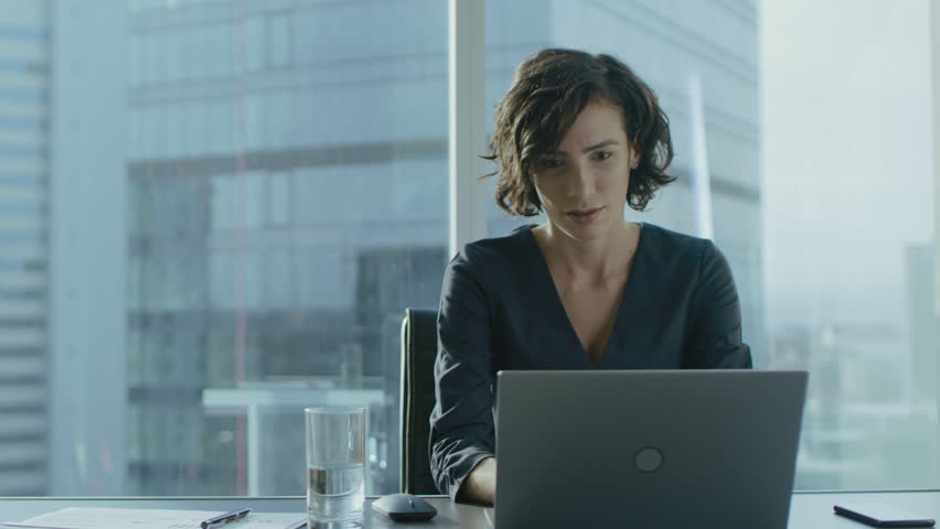 Beautiful Successful Female CEO Works on a Laptop in Her Modern Sunny Office with Cityscape Window View. Strong Female Business Leader. Shot on RED EPIC-W 8K Helium Cinema Camera. | Shutterstock HD Video #1016145742