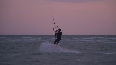 Slow-motion shooting, sport kitesurfer performs tricks on the sunset background