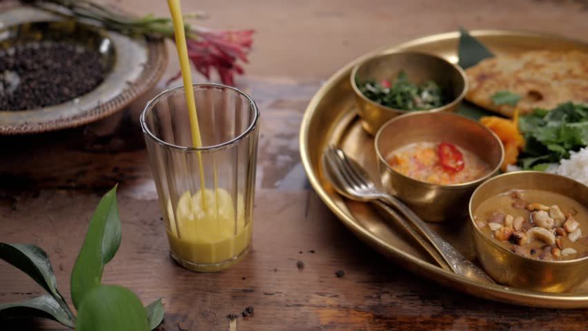 Beautiful and homemade fresh Indian sri lankian drink - mango lassi. On wooden table, garnished with fresh mint. Natural light, with carry traditional food rice