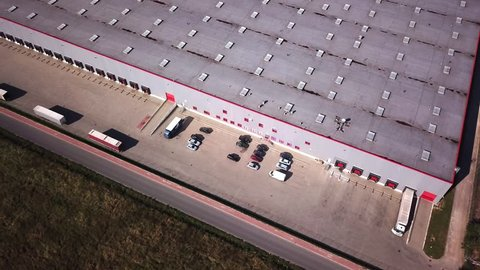 Zoom Out Aerial Shot of Industrial Warehouse/ Storage Building/ Loading Area where Many Trucks Are Loading/ Unloading Merchandise.