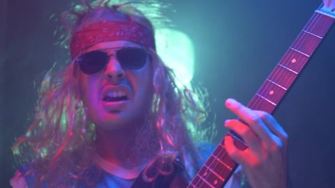 Old style 80s 90s rocker rocking on his electric guitar live. funny clip of a rockstar