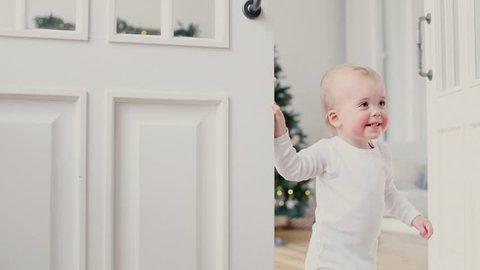 Baby boy peeking out of the open white room door