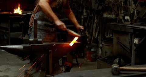 Blacksmith examining a hot metal rod with brush in workshop 4k