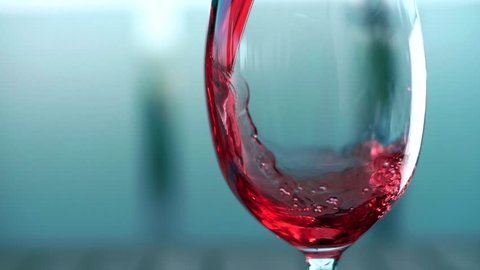 Grape juice is poured into a glass of glass
